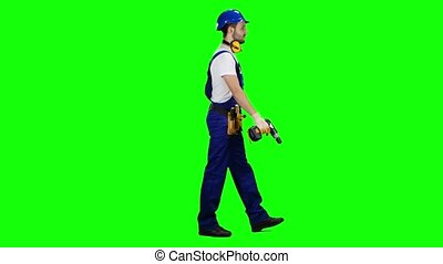 Man working from a construction site comes with a drill in his hands. Green screen. Side view