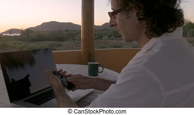Man working from remote office along beach using smart phone...