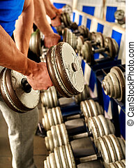 Man working his arms with dumbbells at gym.