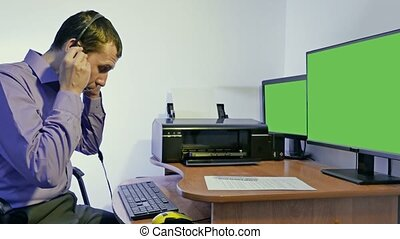 man working in a call center support for computer with headphones and microphone