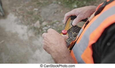 Man Working In Construction Site And Operating Crane Remote