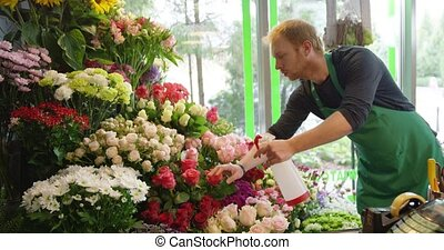 Man working in floral shop - Side view of young man in...