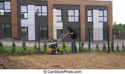 Man working in garden with tiller machine. Cultivated, cultivator. Gimbal motion