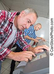 man working in printing house programming printer machine
