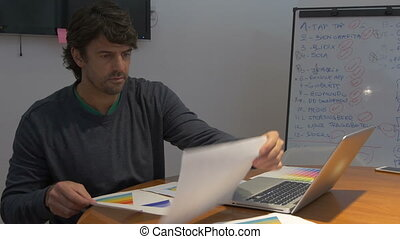 Man working late, sitting office desk laptop computer papers negative emotions depression hands holding head