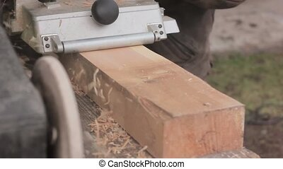 man working on a wood planing machine. Chips fly in different side from the planer
