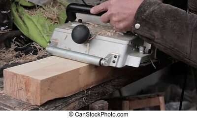 man working on a wood planing machine. Chips fly in...