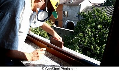 man working on a wooden window