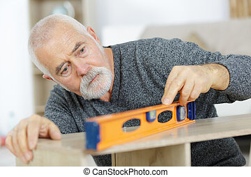 man working on an installation using a leveling tool