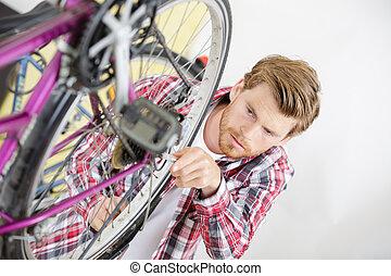 Man working on bicycle wheel