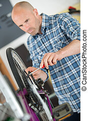 Man working on bicycle with a screwdriver