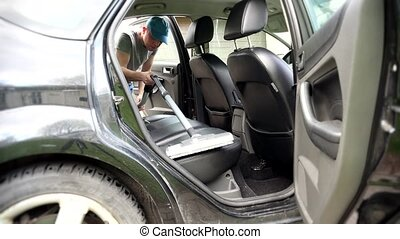man working on client car with vacuum cleaner.