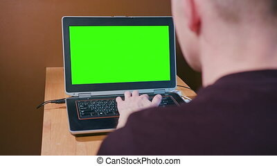 Man Working on Computer with Green Screen