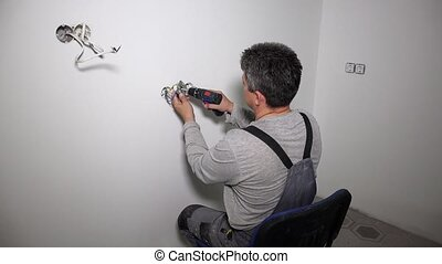 Man working on electrical wall socket wires using cordless screwdriver drill