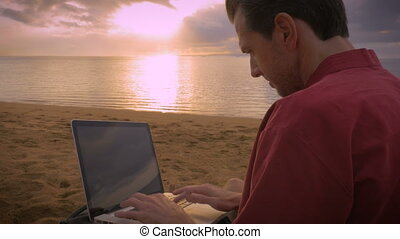 Man working on his laptop on the beach during sunrise drinking coffee