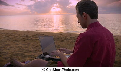 Man working on his laptop on the beach during sunrise or sunset