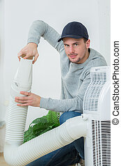 Man working on hose of air conditioning unit