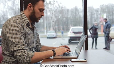 Man working on laptop in cafe. static