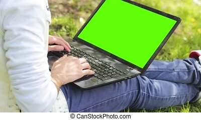 Man working on laptop with chromakey green screen