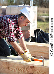 Man working on large wooden structure