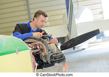 Man working on light aircraft