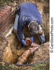 Man Working on Old Clay Ceramic Sewer Line Pipes - Man...