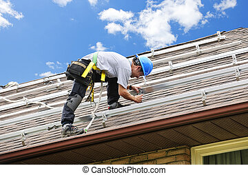 Man working on roof installing rails for solar panels - Man ...
