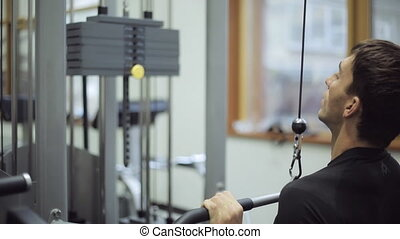 Man working on simulator thrust of upper block in gym. There...