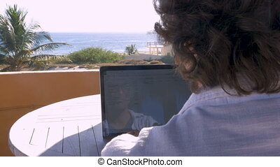 Man working on spreadsheet on computer at home with ocean...