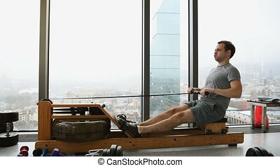 Man working out on row machine in fitness studio at scyscraper luxury hotel gym