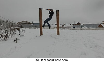 Pullups. Man working out on outdoors sports ground. Young athlete performing street workout warm up. Calisthenics training. Freezing cold winter weather