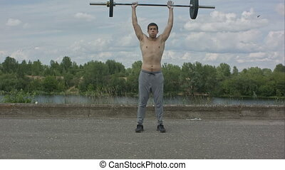 Man working out outdoors with barbell. Professional shot in...