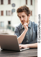 Man working outdoor with a laptop