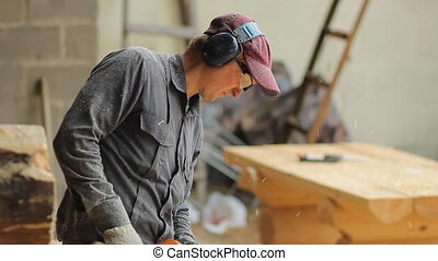 Man working with a chainsaw. Wood shavings are flying saw his face. Close up