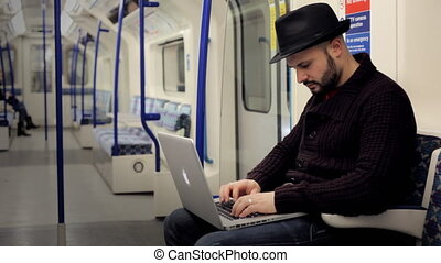Man working with a laptop on a tube