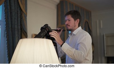 Man working with camera on tripod indoors