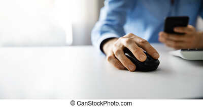 man working with desktop computer and using smart phone in office. copy space