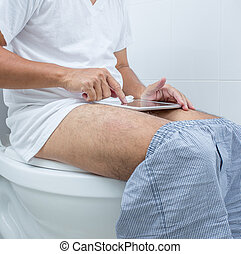 man working with digital tablet while  sitting on the toilet