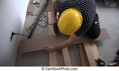 man working with jigsaw and wooden laminate floor panels....