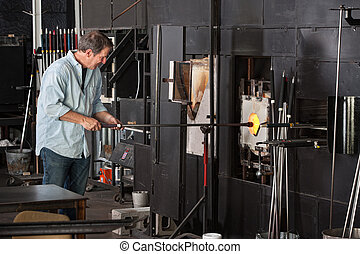 Man Working with Kiln - European male working with kiln in...