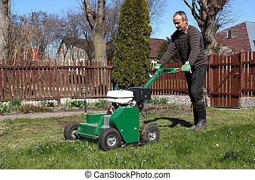 Man working with Lawn Aerator - Lawn Aerator.A lawn aerator...