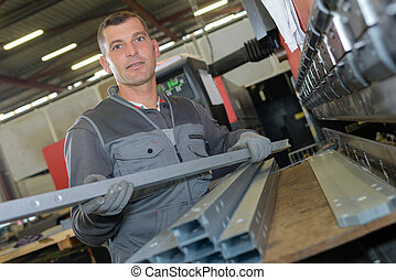 man working with metal bars in factory