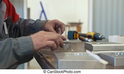 Man working with metal object for manufacturing industrial CNC machinery