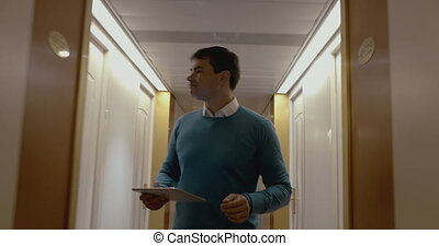 Man working with pad in hotel hallway