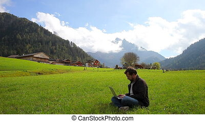 Man working with pc in mountain