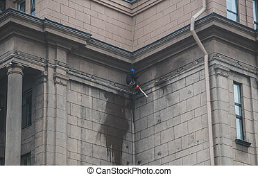 Man working with pressure washer on the wall of the building.
