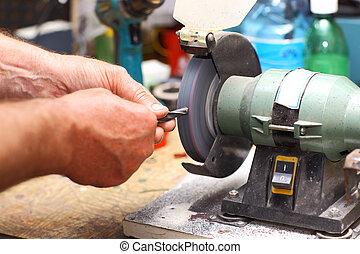 Man working with sharpening machine tool - Detail of hands...