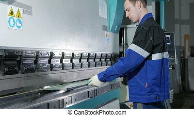 Man working with sheet metal on CNC hydraulic press brake....