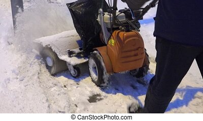 Man working with snow blowing machine on pavement after snow fall in winter. 4K