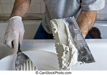 Man Working with Trowel and Mortar Tiling a Bathroom Wall. ...
